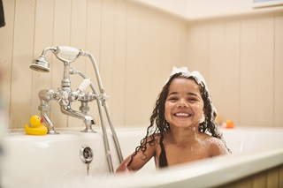 A child cheekily grinning in the bath