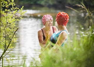 Two ladies laughing in a rural river
