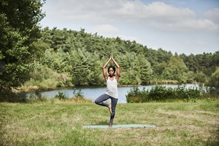 A lady doing the tree pose, also known as the Vrksasana, in a rural setting