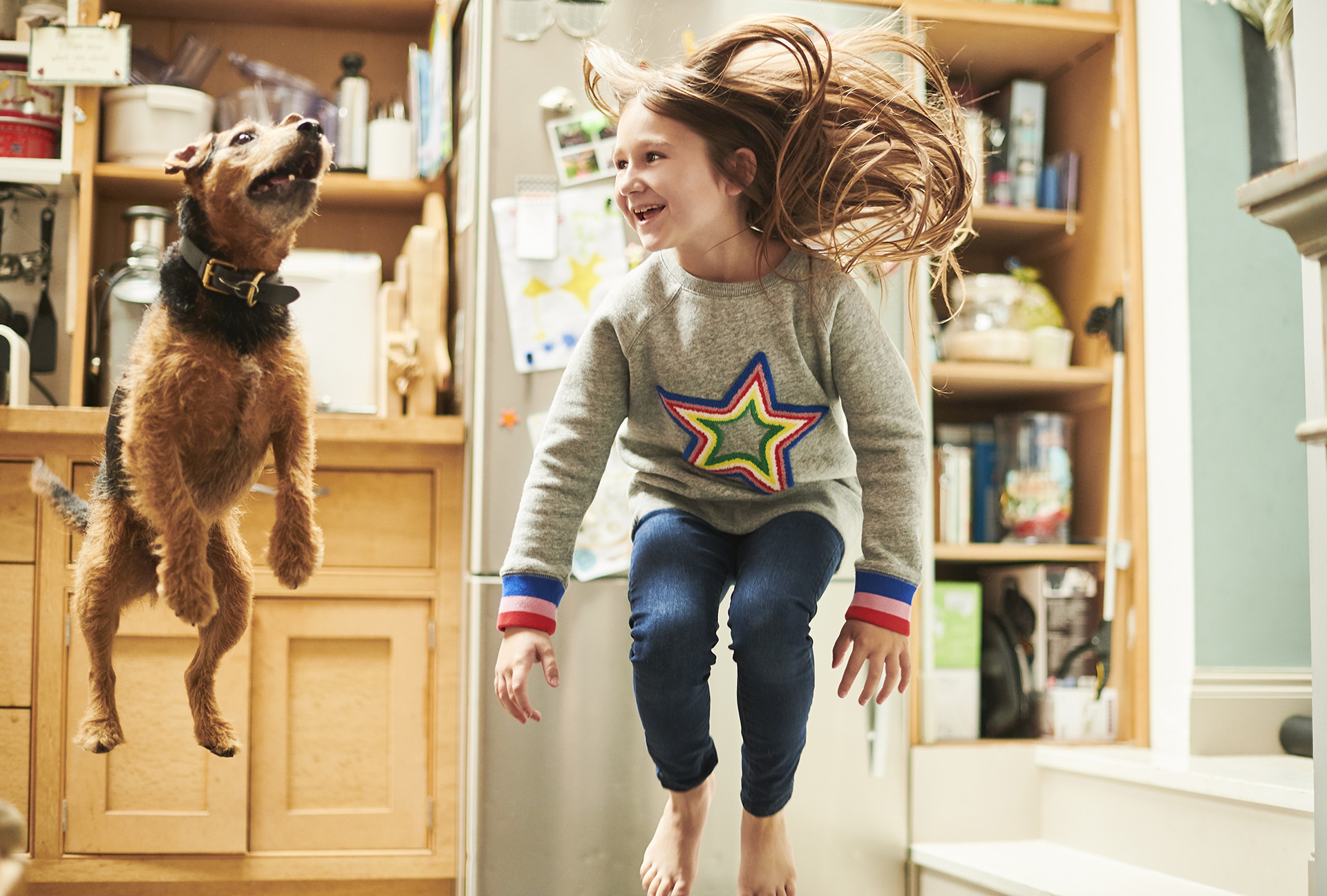 A young girl and her dog jumping in their kitchen