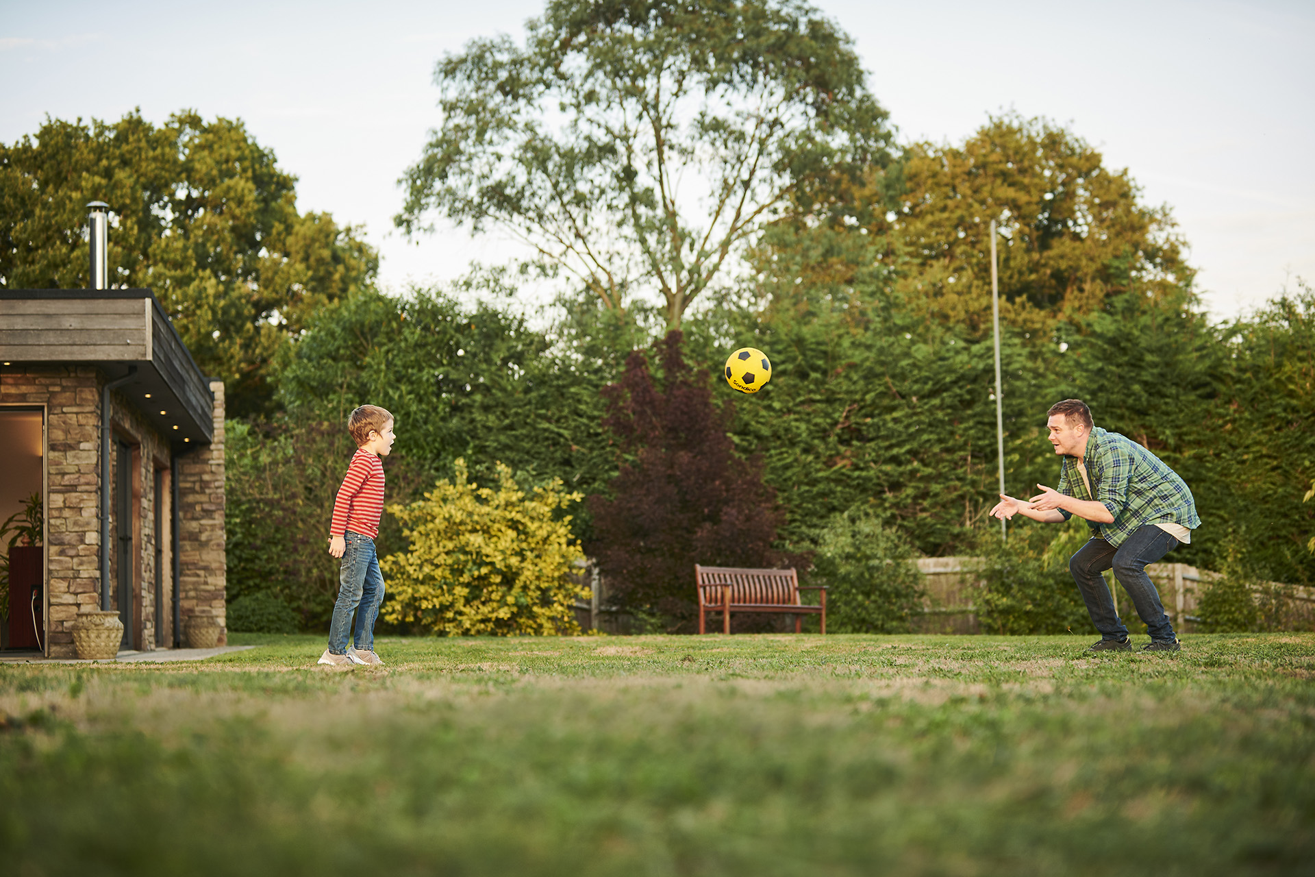 A man and his son playing catch in their garden