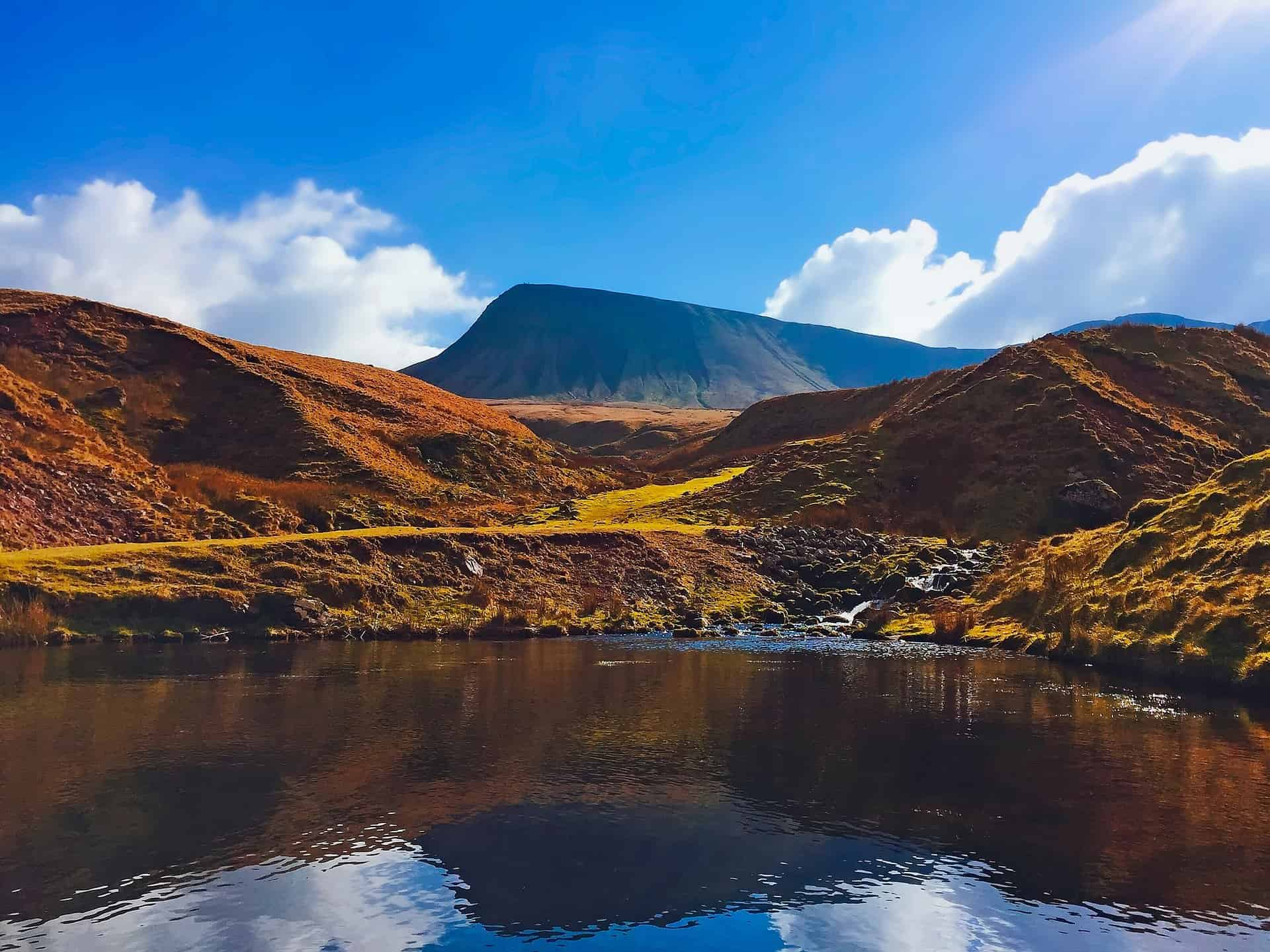 A landscape image of a lake and hills on a sunny day in the UK