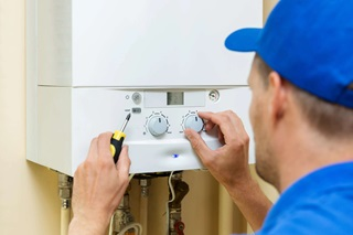 Engineer in a blue hat servicing a LPG boiler