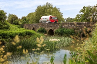 A Calor Gas truck driving over a bridge in the countryside
