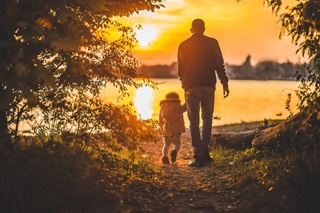 Father and child walking towards the sunset on a lake