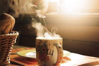 Mug of hot drink with steam coming out the top in a cosy room with sunlight shining in
