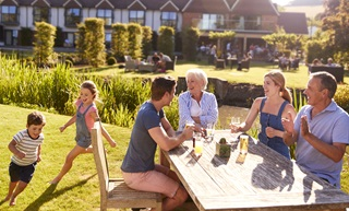 A group of people smiling and drinking on a table outside in a pub garden