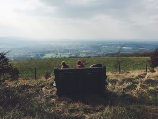 Three people wearing wolly hats sat on a bench facing a beautiful countryside view