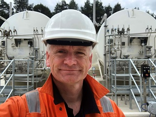 Calor employee Paul Smith wearing a high vis jacket and hard hat outside a Calor plant