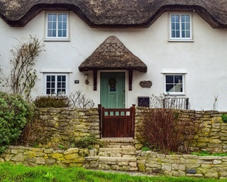 White countryside cottage with a thatched rood and green door.
