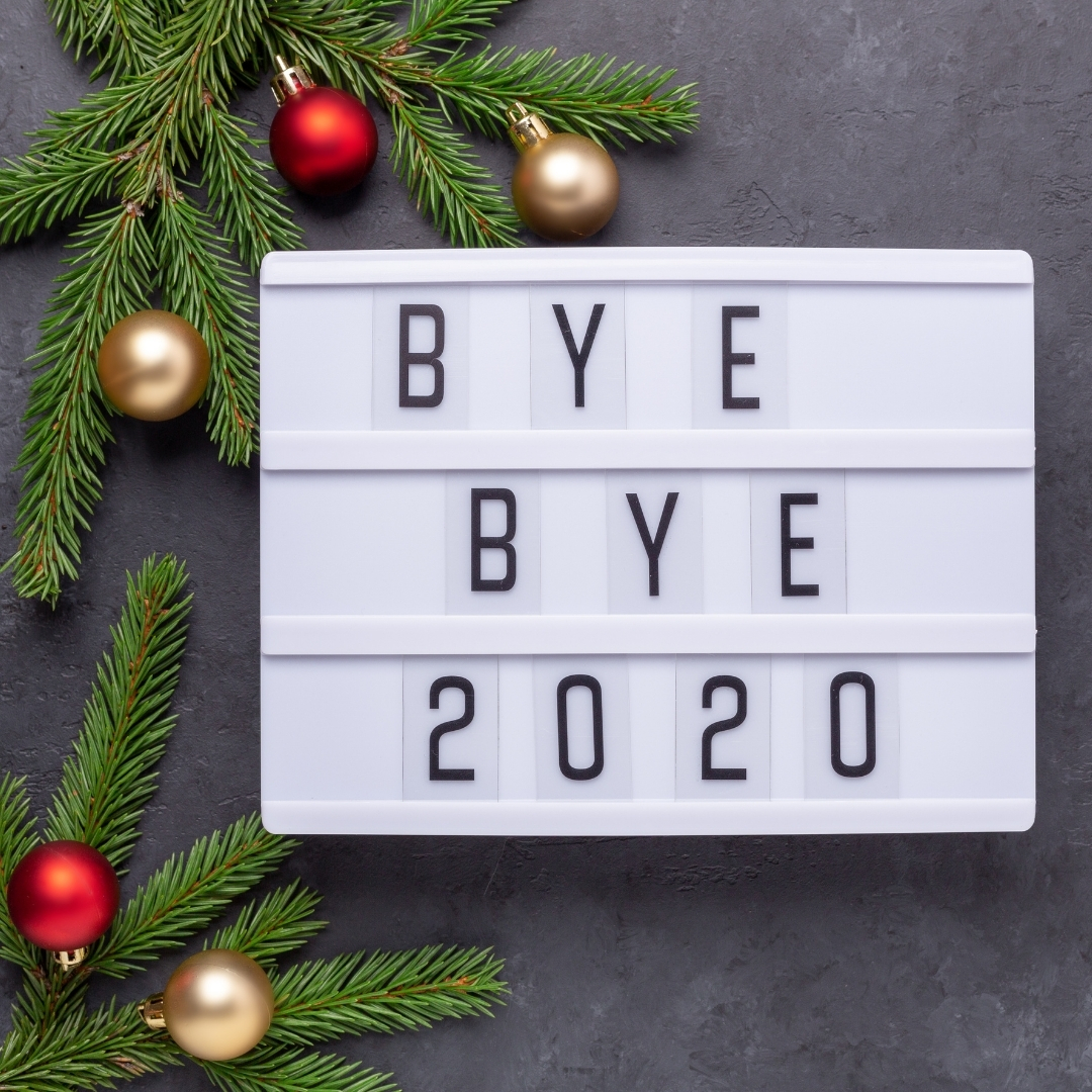 "A light box with ""bye bye 2020"" in letters, baubles and christmas tree brnaches surrounding"