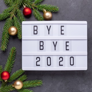 """A light box with """"bye bye 2020"""" in letters, baubles and christmas tree brnaches surrounding"""