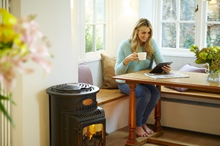 A lady sitting beside a Calor portable gas heater
