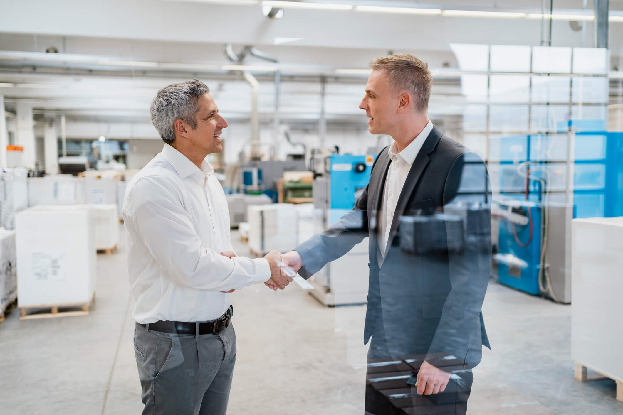Two business men in manufacturing shaking hands