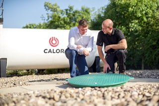 A Calor employee and customer talking beside an LPG underground tank cover