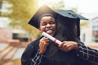 Two beaming graduates hugging