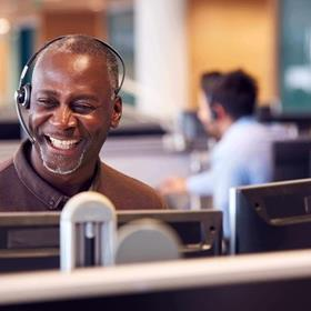 Man wearing a headset, smiling, at a computer in a call centre / telesales department