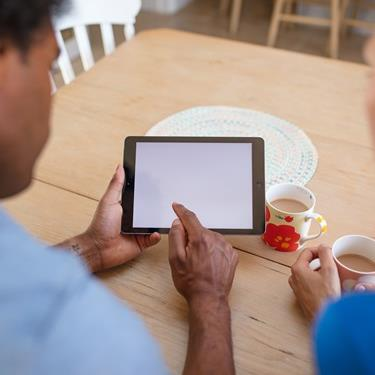 A couple sitting at their dining table, looking at their tablet