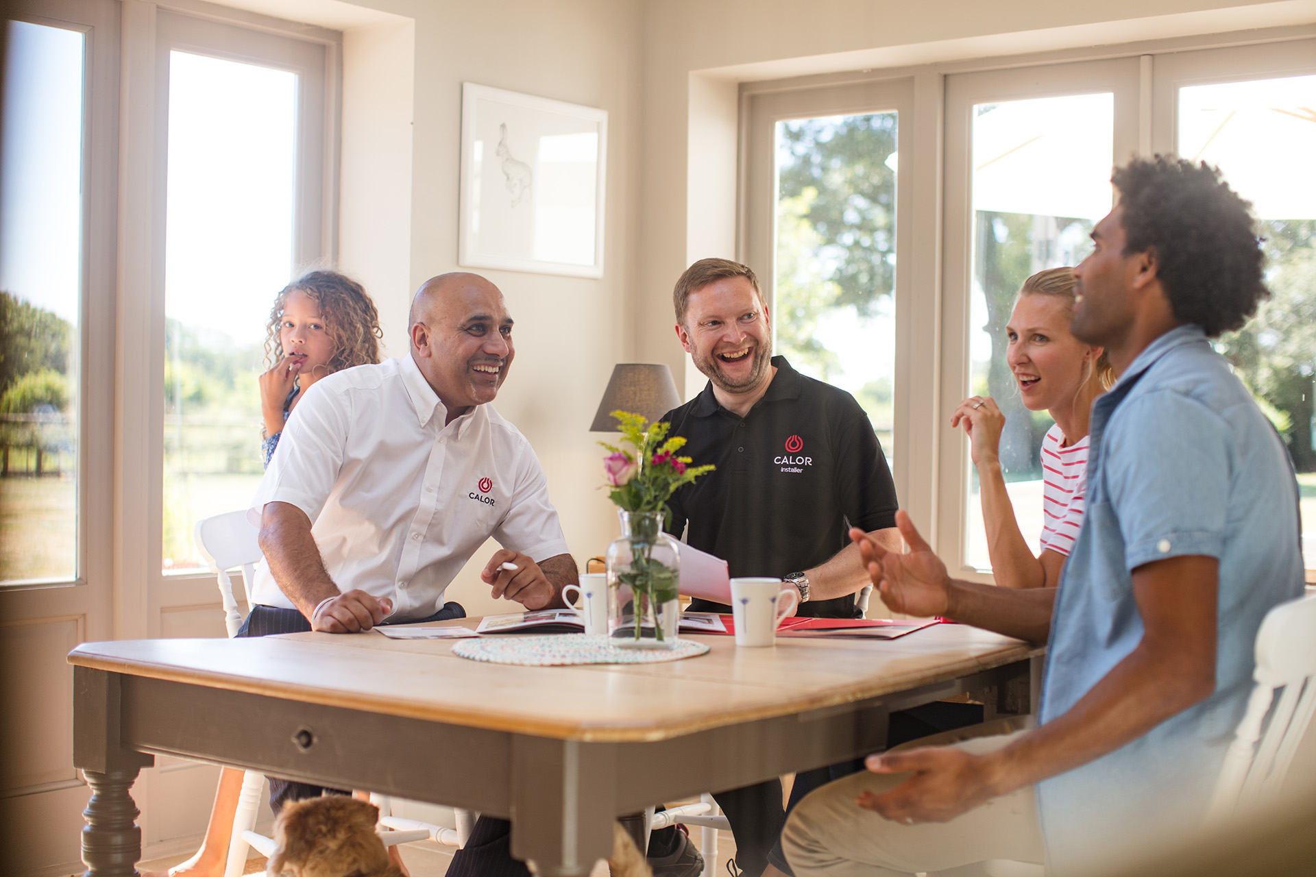 Two Calor employees and two Calor customers laughing around a kitchen table