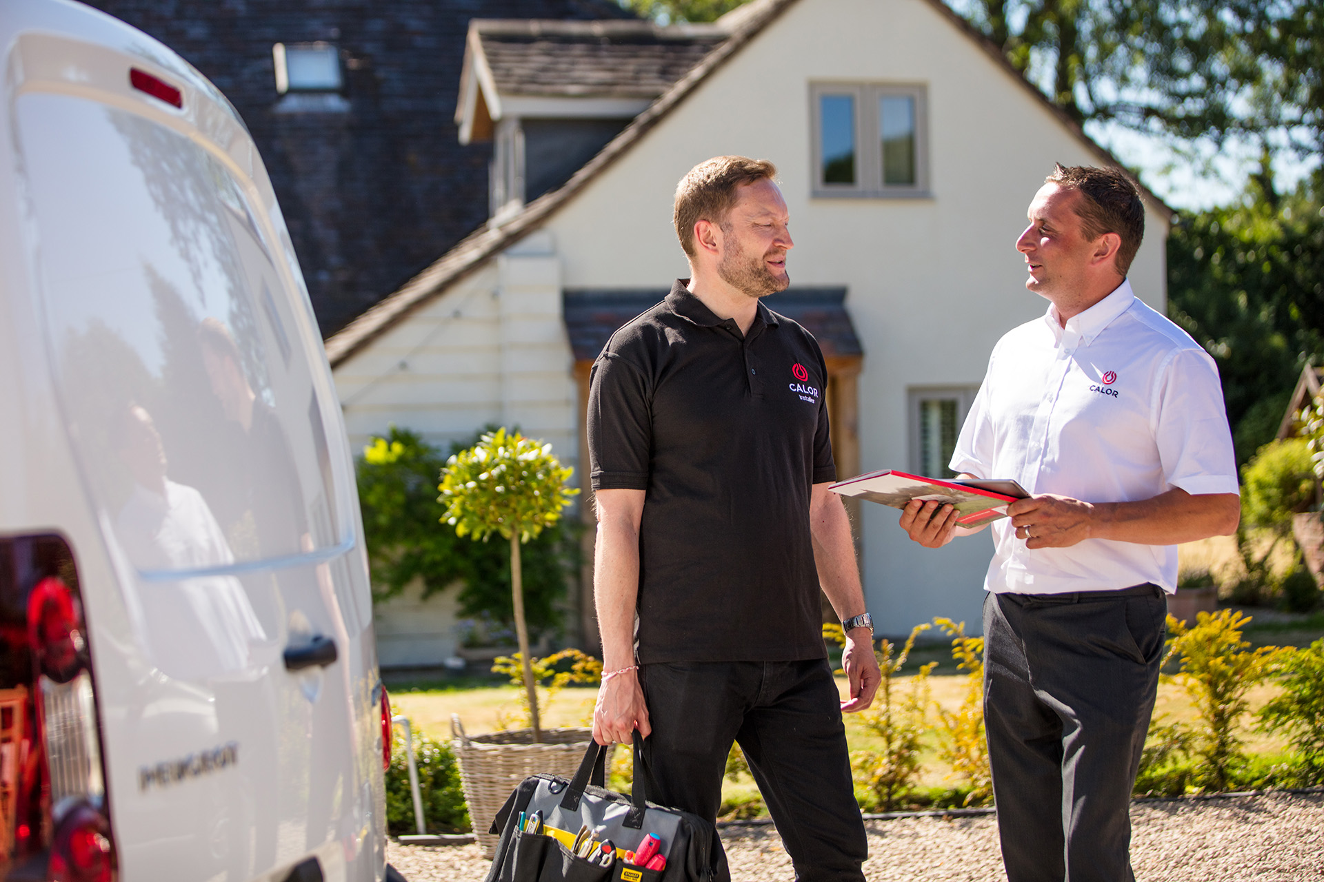 Two Calor employees talking outside of a Calor customer's home