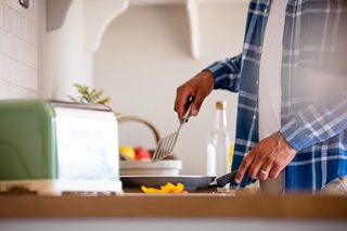 A close up of a man frying vegetables in his kitchen