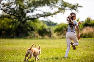 A child running away from her dog in her garden