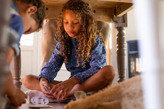 A young girl playing cards with her brother underneath their kitchen table