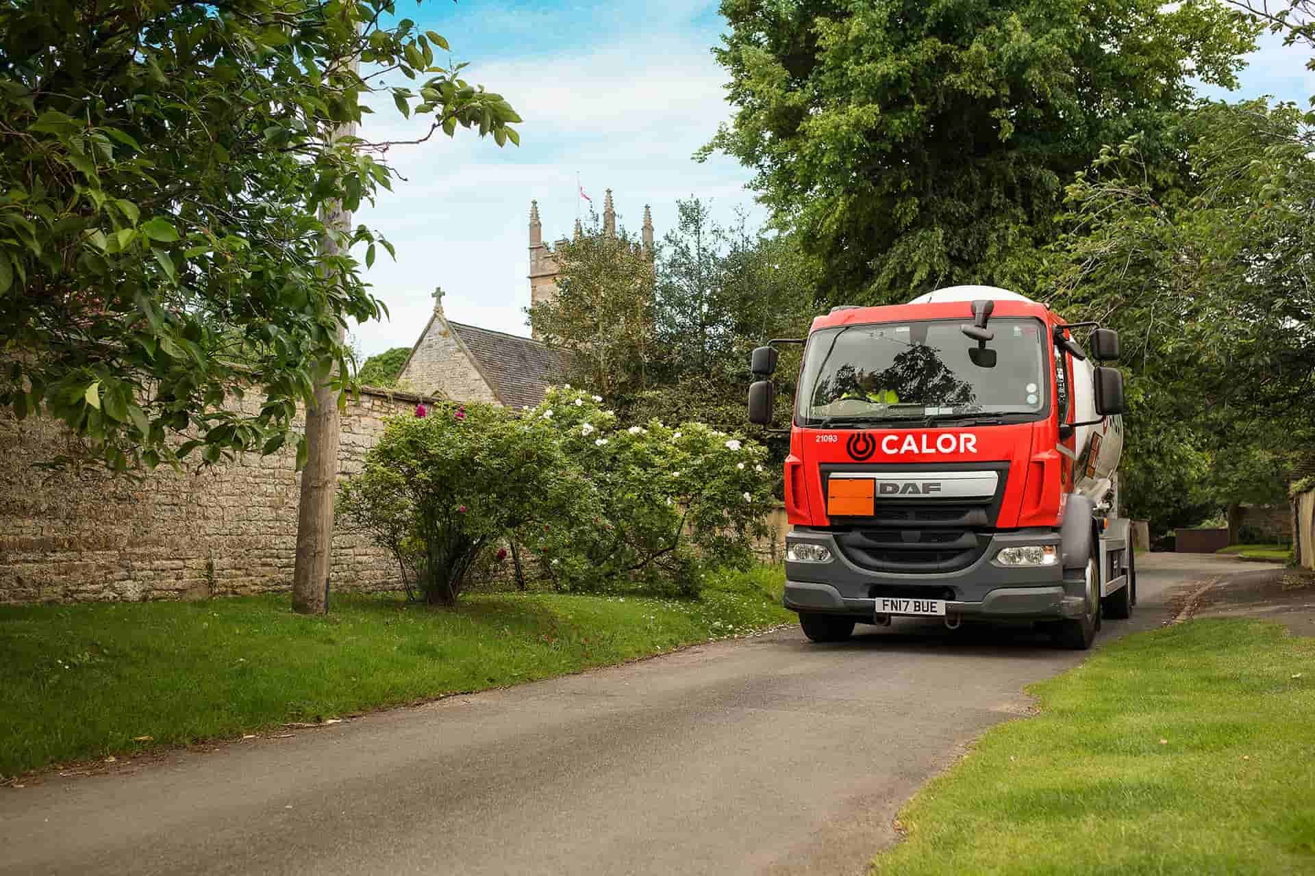 A front view of a Calor lorry driving through a village