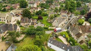 An aerial view of a Calor lorry driving through a rural village