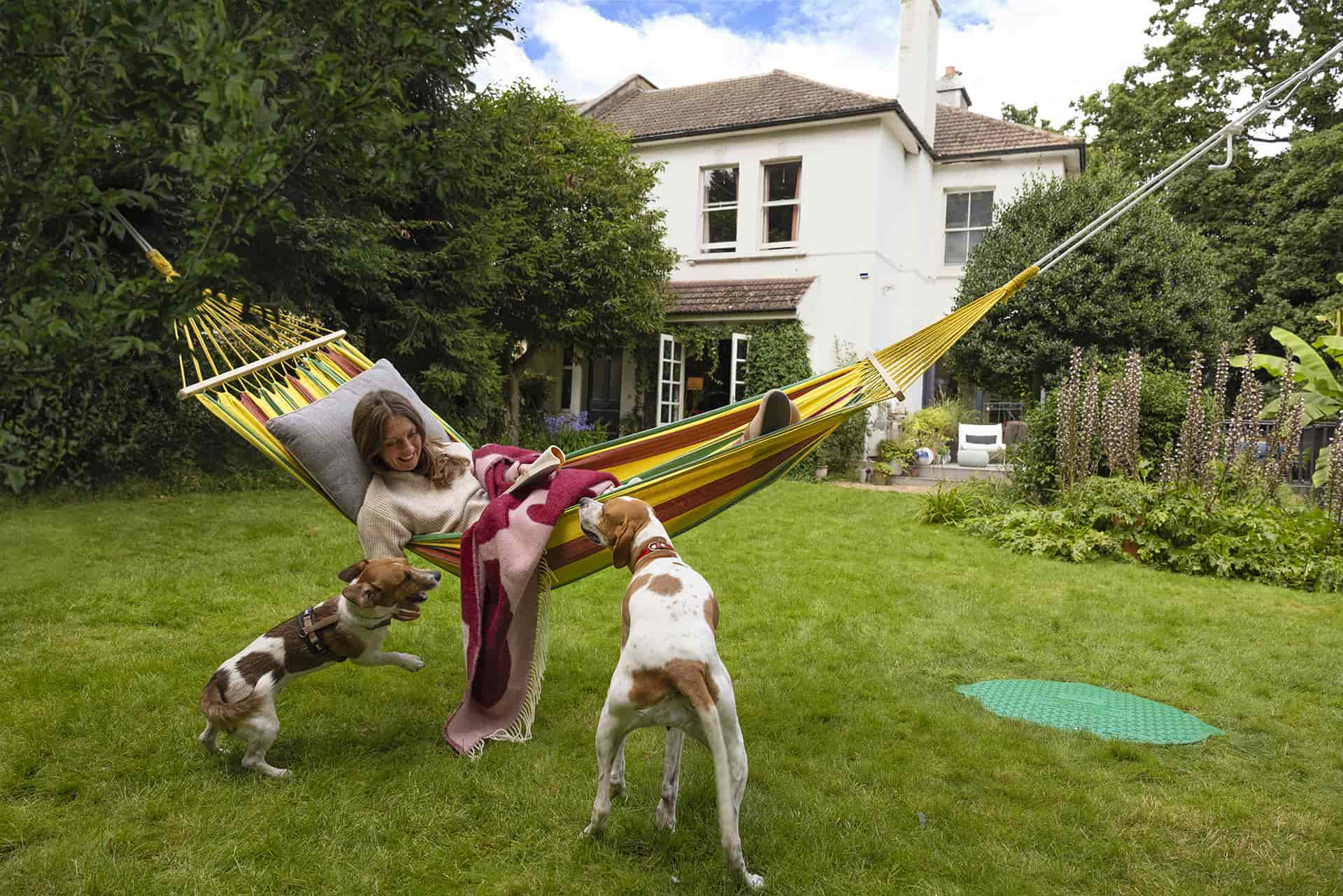 A lady in her garden on a hammock with her two dogs, in the background you can see a underground tank and her rural home