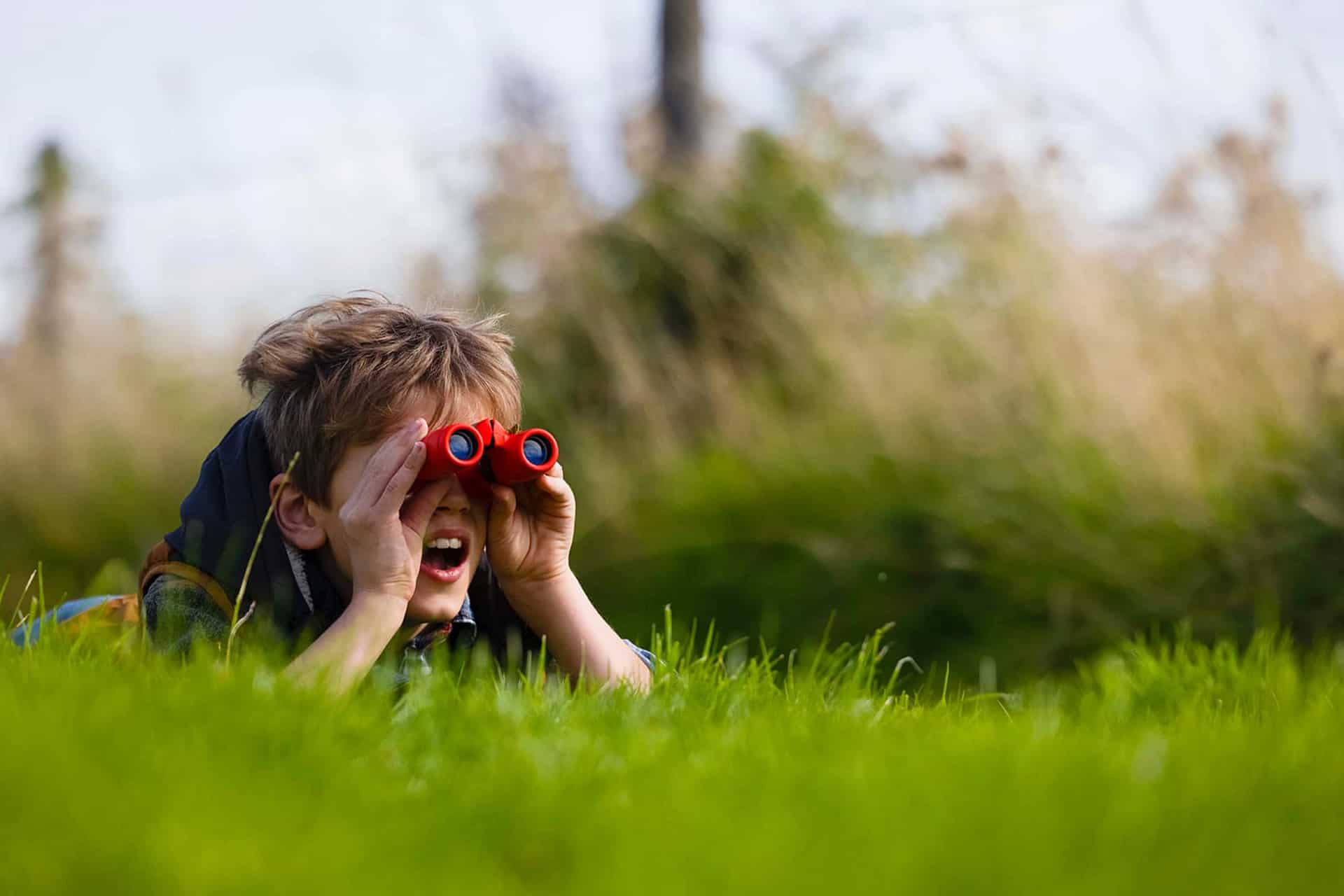 A boy lying in the grass looking through binoculars