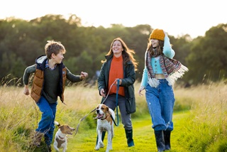 A woman, her two children, a girl and a boy and their dogs walking through a field, laughing and smiling, wearing coats and hats