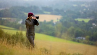 A woman taking pictures in the countryside