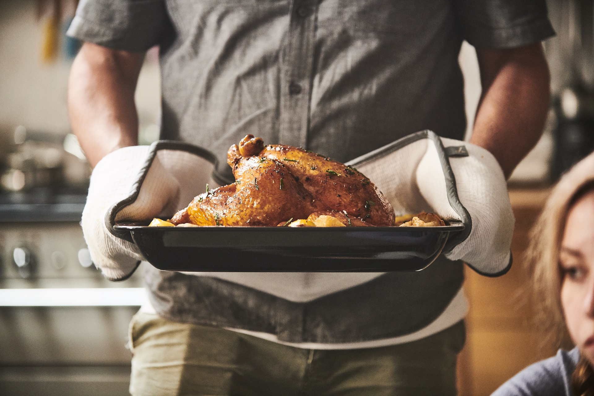 Roast chicken in an oven tray held by a man wearing oven gloves