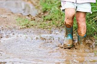 Small child splashing in muddy puddles wearing wellington boots