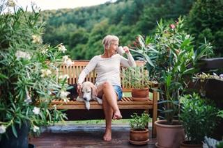 A senior woman with a dog on a garden bench drinking tea