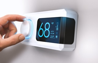 Person adjusting thermostat on wall to 68 degrees Fahrenheit