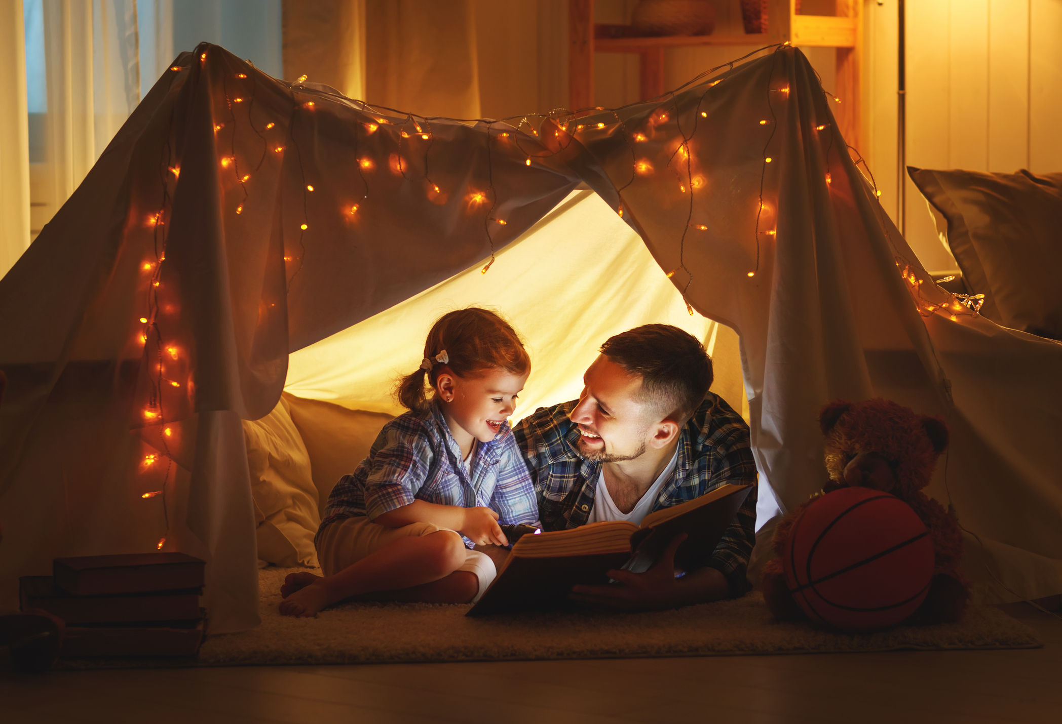 Father and daughter reading a book in an indoor tent