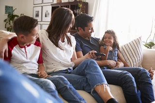 Family of mom, dad, one young girl and one young boy sitting together on a couch and smiling