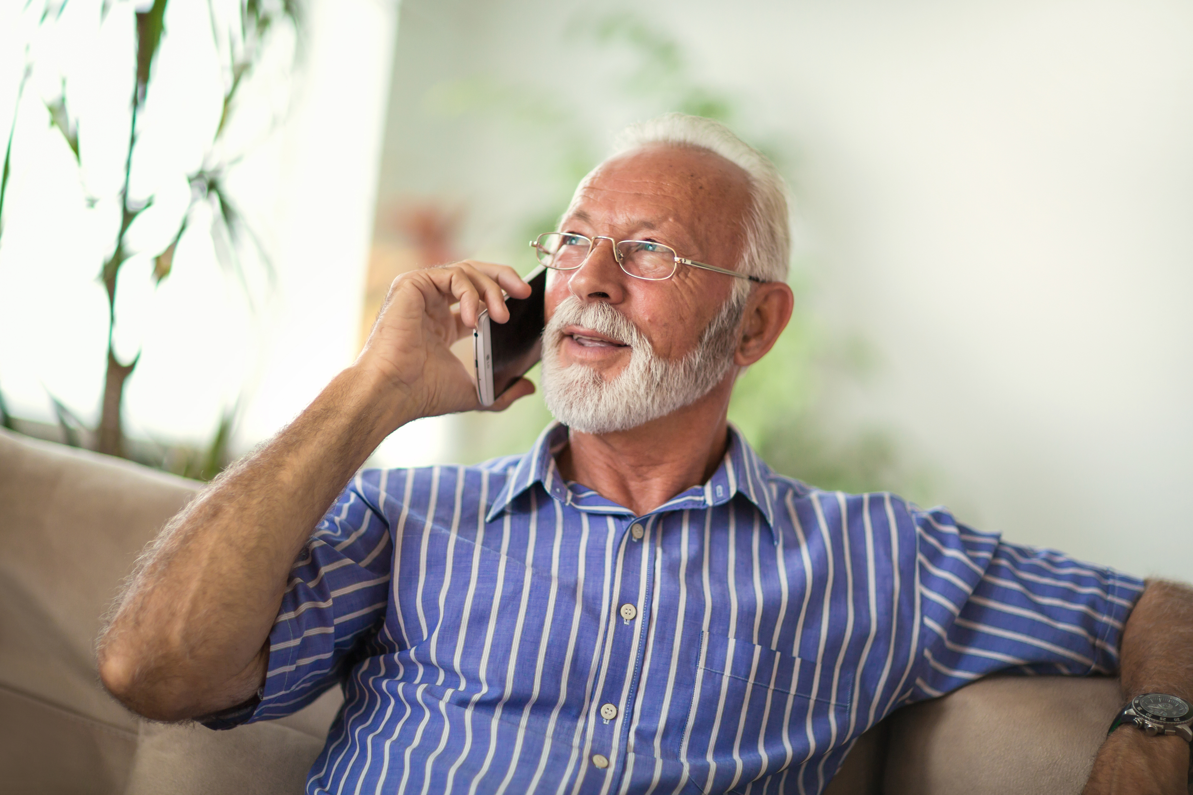 Elderly man sitting on the couch and talking on a mobile phone