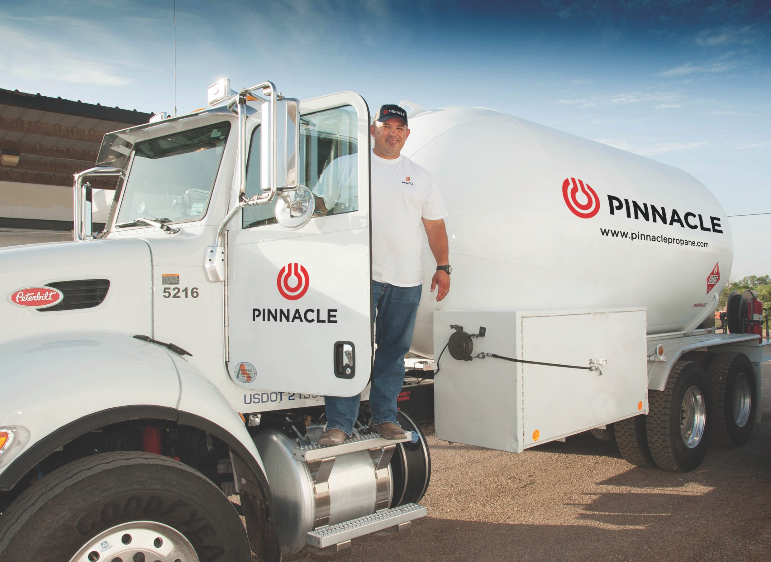 Smiling man wearing baseball hat standing in the door of a propane bobtail truck