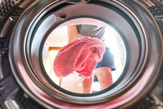 Woman throwing a pink towel into dryer