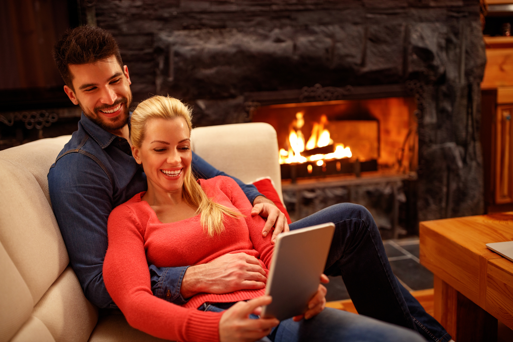 Man and woman sitting on the couch looking at a tablet next to a fireplace