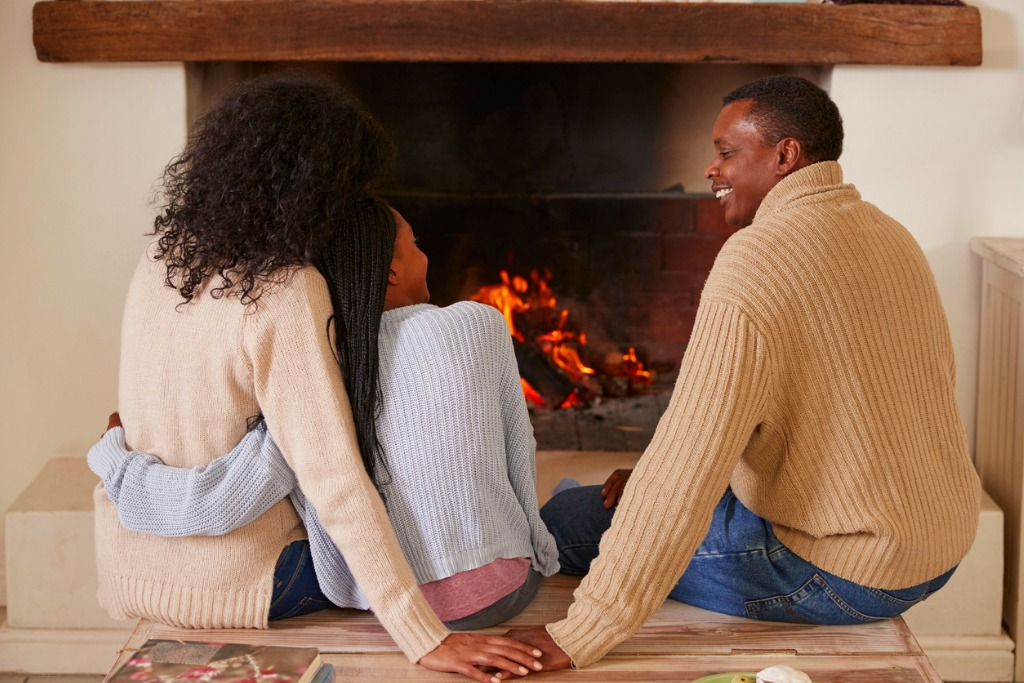 Parents sitting with daughter next to fireplace